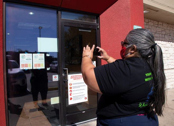 Gloria Vera-Bedolla, an admissions representative for Central Texas Allied Health Institute, tapes  to store windows flyers in both English and Spanish about a COVID-19 vaccination clinic.