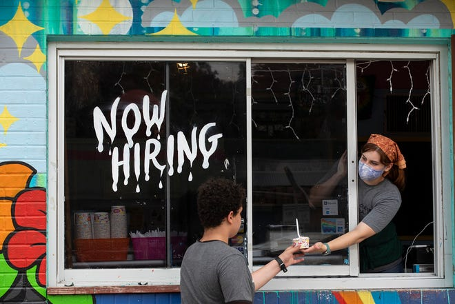 Employee Rae Bennett hands a scoop of ice cream to a customer Friday at Amy's Ice Cream on South Congress Avenue. Employers in the Austin metro area added more than 8,000 workers to payrolls last month as the pandemic's grip eased.