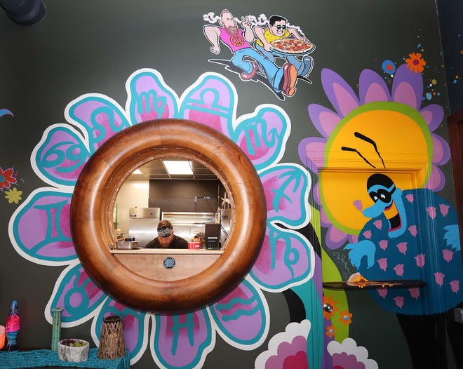 John Taylor and Ari Vandendriessche, owners Totally Baked Pizza, prepare food in Akron. The murals covering the walls, including the caricature of Taylor and Vandendriessche, top, were painted by brothers and Akron artists Mike and Chuck Ayers.