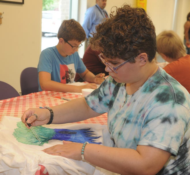 Shannon Bowman, 17, uses an eye dropper to apply rubbing alcohol to artwork on a T-shirt on Tuesday, July 13, 2021, at Rodman Public Library during the Teen Paint & Tie Dye event.