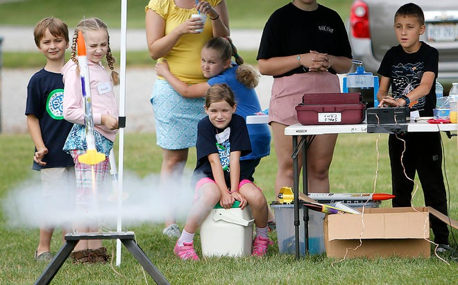 Austin Miller, right, pushes the controls to launch his rocket as Graham Gibson, Joscelyn Bennett, McKenna Bennett, holding on to her mother, and Elizabeth Yordy watch during the launch day for Mr. Lee's Space Camp on Friday at the Ashland Soccer Complex. TOM E. PUSKAR/TIMES-GAZETTE.COM