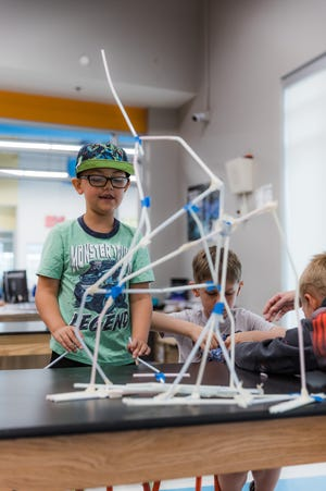 Students work on building the tallest straw tower in the ConocoPhillips STEM Lab at the Bartlesville Boys & Girls Club.