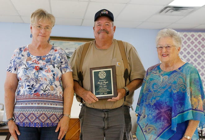 Randy Feight, chief of the Lake Brownwood Bridge Volunteer Fire Department, stands between Jolly Elders members Evelyn Newman (left) and Sue Crow. The Jolly Elders presented Feight with a plaque of appreciation for his service as chief.