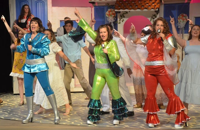 """The wedding of the daughter of one of three longtime friends brings them back together in the Lyric Theatre's production of """"Mamma Mia!"""" The musical's storyline is built around the hit music of the Swedish group ABBA. Pictured from left to right leading the cast in one of the songs are Tommie Bailey as Tanya, Billie Harvey as resort owner Donna, and Shannon Lee as Rosie. The show opened Friday night, and continues on Fridays, Saturdays, and Sundays through July 25."""