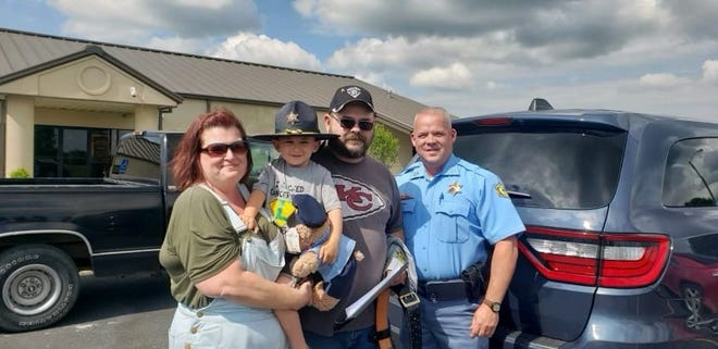 Logan Ward (in Sheriff's hat) with his family and Sheriff Monty Hughey (right)