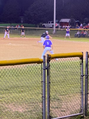 A Little Giant keeps an eye on the Wildcat pitcher as he waits for an opportunity to head to home.