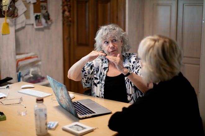 """Randi Cohen, left, helps Donna Greenman with a computer issue. They are both part of a group, Care and Share Time Bank, that allows people to do services for others and then """"spend"""" those hours to have other members help them with things."""