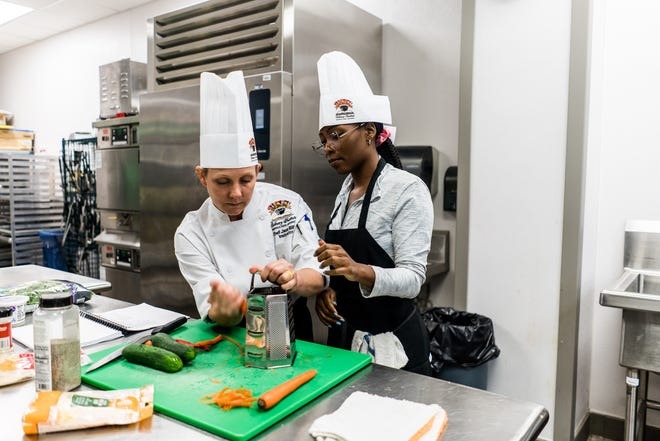 Chef Jana Billiot, an instructor at Nicholls' Chef John Folse Culinary Institute, shows LSU medical student Lauren Jackson how to grate carrots to prepare for the day's recipes focusing on children's health and nutrition.