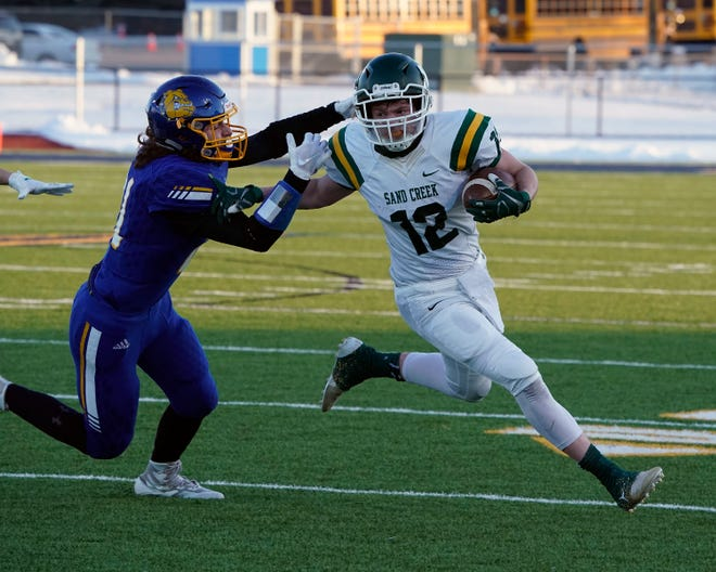 Sand Creek's Will Alexander (12) stiff arms Centreville's Matt Lorencz during their Division 8 regional final on January 10.