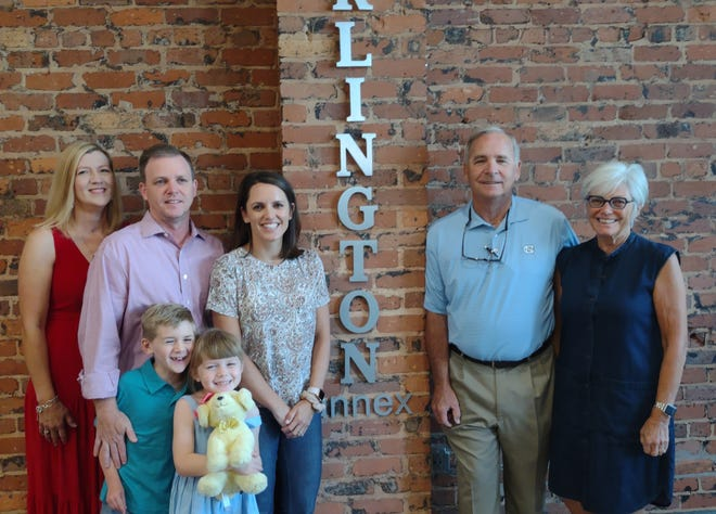 Mike and Paula Turlington, along with their children and grandchildren, celebrated the unveiling of the new annex to the Edward C. Smith Civic Center on Friday, which was named after them because they donated the building next door to the theater.