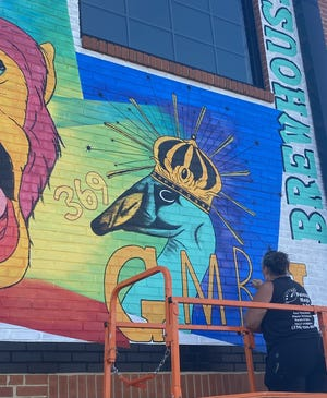 Beth Stewart, owner of Painted Magic by Beth, works on a new mural on the exterior wall at Goose & the Monkey Brew House in the Historic Depot District in Lexington.