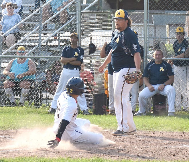 Noah Carpenter slides across the plate with the first Ilion Post run against Adrean Post during Thursday's District V American Legion playoff game. Adrean Post pitcher Matt St. Louis is covering the plate.