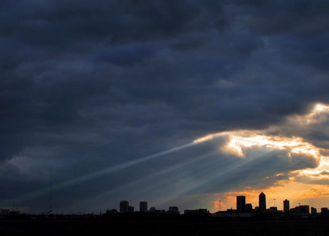 Sunlight streams through a blanket of heavy clouds over the downtown Jacksonville skyline.