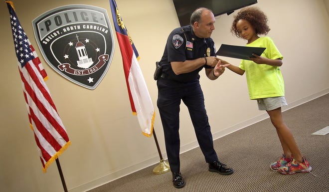 Chief Jeff Ledford gives a certificate to eight-year-old Harmonye Jenkins during a graduation ceremony on the last day of Cop Camp Friday morning, July 16, 2021, at the Shelby Police Department on West Warren Street in Shelby.