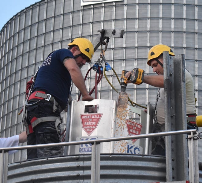 On Tuesday, July 13, area firefighters trained with the Great Wall of Rescue panels for use with farmers trapped in grain bins. After placing panels to encircle Kewanee City firefighter Jake Forney, another Kewanee City firefighter, Rob Horn, left, steadies the panels while Kewanee Community firefighter Ellis Ericson, right, uses a drill to power an auger to remove grain inside the panels. Forney had been buried in grain up to his waist for the demonstration. The training was at Gold Star FS Germans Corner elevator, rural Kewanee.