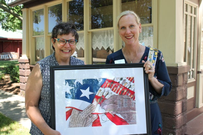 Local artist Carolyn Stich (left) showcases her award-winning poster with Regent Christine Hoek of the Holland DAR Chapter.
