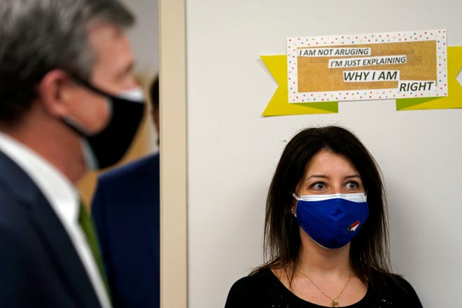 Gov. Roy Cooper, left, answers questions Thursday, Jan. 28, 2021 in Pittsboro, N.C. while Secretary of the N.C. Department Health and Human Services Dr. Mandy Cohen listens at right during a tour of Piedmont Health Senior Care. Cohen, who got the single-dose Johnson & Johnson vaccine, is calling on individuals who got the Pfizer, Moderna or J&J vaccines to explain to loved ones why they chose to get the shot.  (AP Photo/Gerry Broome)