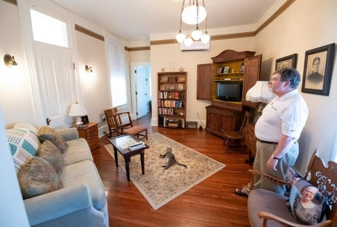 Wes Bartlett stands in his living room which is modeled in the original 1888-style of the building, on June 8, 2018. Wes and his wife Gwen Bartlett own Bookends as well as these apartments above their shop which used to be a hotel named 'The European Hotel' built in 1887.