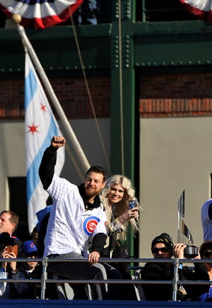 Chicago Cubs baseball player Ben Zobrist pumps his fist while his wife, Julianna, looks on outside Wrigley Field in Chicago during a parade honoring the World Series champions on Nov. 4, 2016.