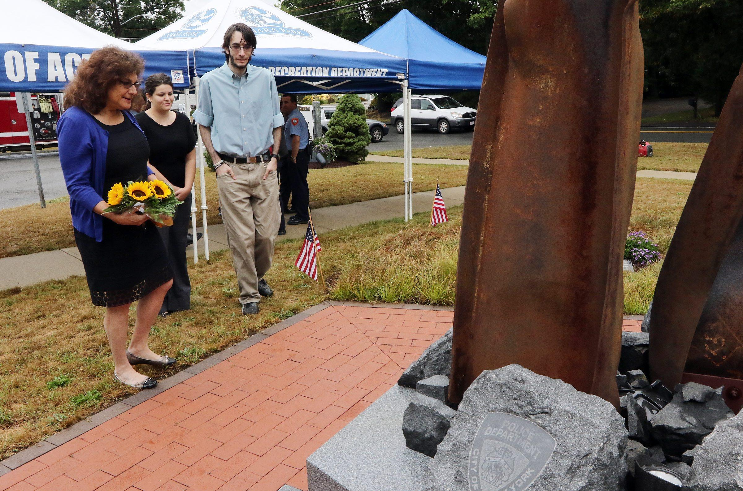Lauren Rosenzweig Morton, the widow of 9/11 victim Philip Rosenzweig, attends a remembrance ceremony at the Acton Sept. 11 memorial in 2015, accompanied by her son and daughter-in-law.