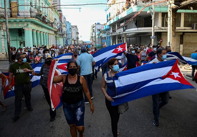 """People take part in a demonstration to support the government of the Cuban President Miguel Diaz-Canel in Havana, on Sunday, July 11, 2021. Thousands of Cubans took part in rare protests Sunday against the communist government, marching through a town chanting """"Down with the dictatorship"""" and """"We want liberty."""""""