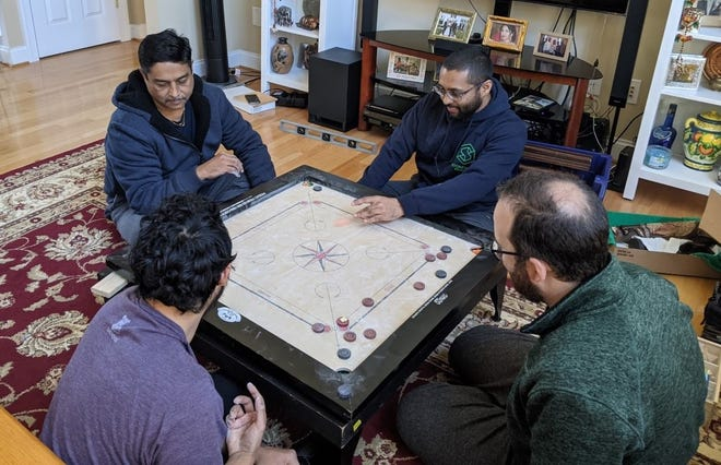Harish Doshi plays carrom with family members in Chester, Va. In the back from left to right, Harish and Jay. In the front from left to right, John and Dev.