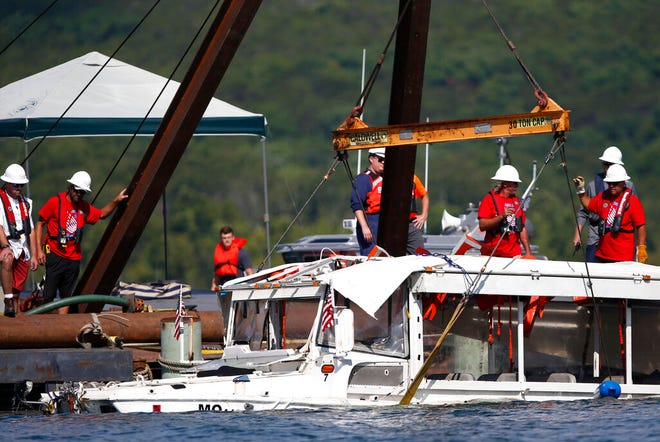 FILE - In this July 23, 2018 file photo, a duck boat that sank in Table Rock Lake in Branson, Mo., is raised after it went down the evening of July 19 after a thunderstorm generated near-hurricane strength winds, killing 17 people. A county prosecutor and Missouri Attorney General Eric Schmitt filed state charges, Friday, July 16, 2021, against three employees of the duck boat tourist attraction in connection with the boat sinking. Nathan Papes/The Springfield News-Leader via AP