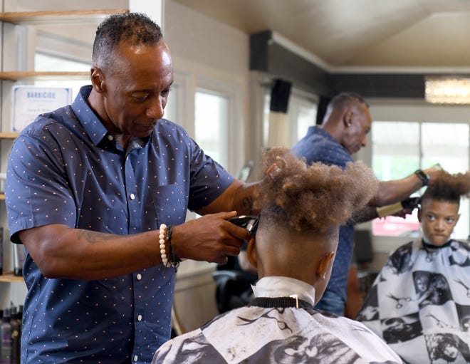 Aaron Williams, who retired from the Canton Police Department last in 2020 after 25 years, cuts the hair of Noah Tuck, 10, at his studio, Abduz Stylz, located at Designer Studios in Canton. Friday, July 16, 2021.