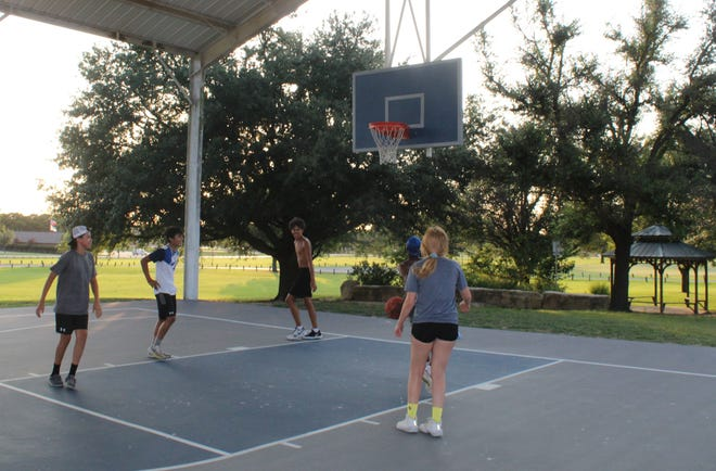 A group of local youths enjoys the cooler evening hours and practice their basketball skills at Stephenville City Park.