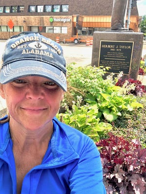 Tracy Menard in front of the Rotary Garden that she volunteers to maintain.
