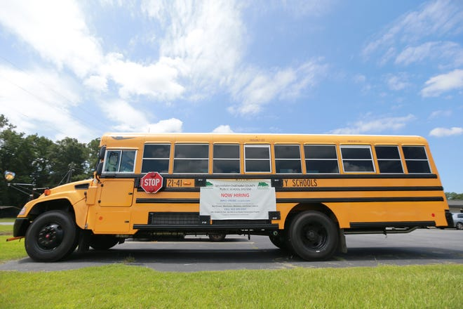 A Savannah Chatham County Public Schools bus sits along highway 80 with a Now Hiring banner on its side.