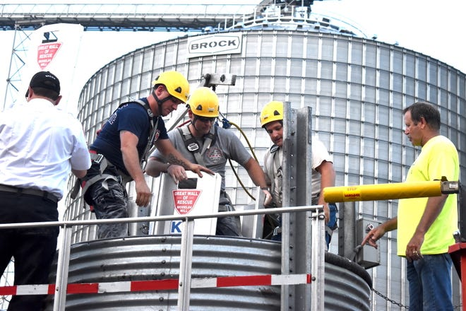 Gold Star FS hosted grain bin rescue training on Tuesday, July 13, at its Germans Corner elevator in rural Kewanee. Kewanee City firefighter Jake Forney, center, volunteered to be buried in corn up to his waist. Firefighters Rob Horn, left, and Ellis Ericson, right, placed Great Wall of Rescue panels around him and used an auger to remove corn from inside the panels until they could remove a panel and let Forney step out. Kewanee Fire Chief Kevin Shook, far left, watches the demonstration as instructor Jeff Sanderfield, far right, explains what's going on.