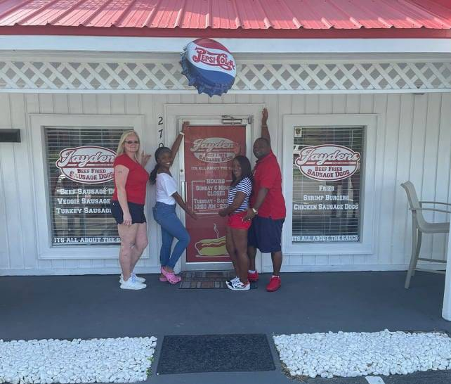 Kathy Taylor, owner of Jayden's Deep Fried Sausage Dogs, is pictured with her husband Deval, their daughter and staff member Stephanie at their location of 2700 Trent Road in New Bern.