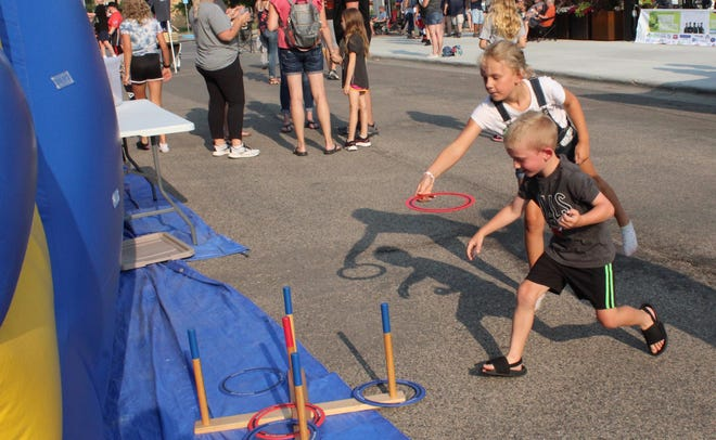Ella Brick and Cullen Zimmer enjoy a friendly game of ring toss before the Downtown Concert Thursday.