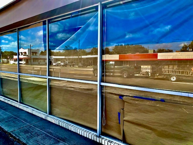 """Northwest Eighth Avenue is reflected in the window of a vacant building on the """"stroad."""""""