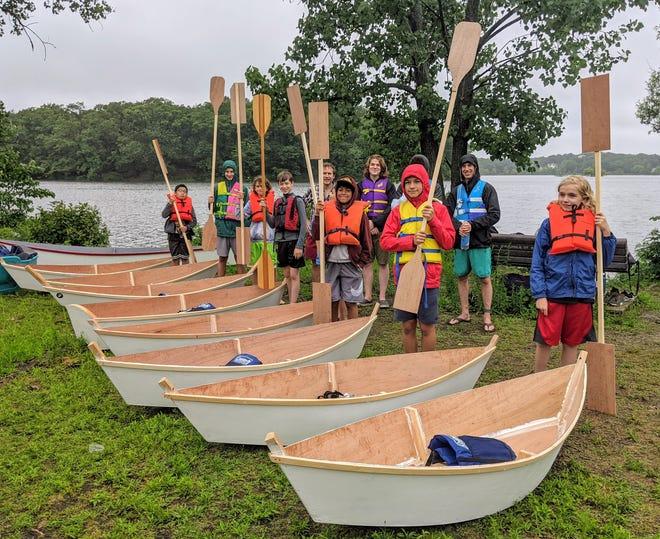 Acera School boat-building students prepare to launch their vessels in Horn Pond. Pictured, from left: Harry Zhou, Quinn Shanley, Alex Colvin, Jonathan Gilmer, Maanav Prakash, Ezra Schwarz-Bart, Tristan Samuel and Quinn Shriver.