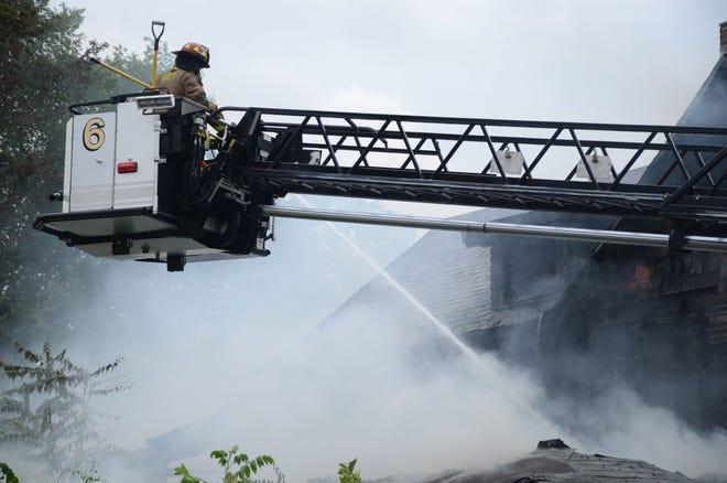 Battle Creek firefighters attack the fire Thursday on West VanBuren Street from an aerial truck.