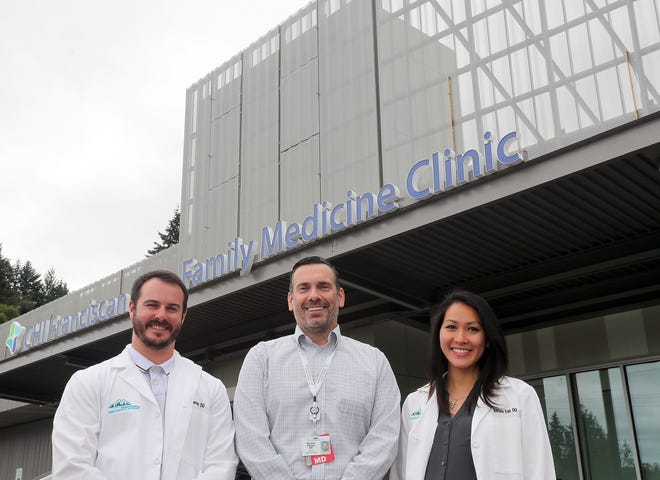 Virginia Mason Franciscan's residency program director Dr. Michael Watson, center, is flanked by recently graduated residents, Dr. Casey Kernan, left, and Dr. Khuyen Tran, right, at CHI Franciscan Family Medicine Clinic in Bremerton Friday.