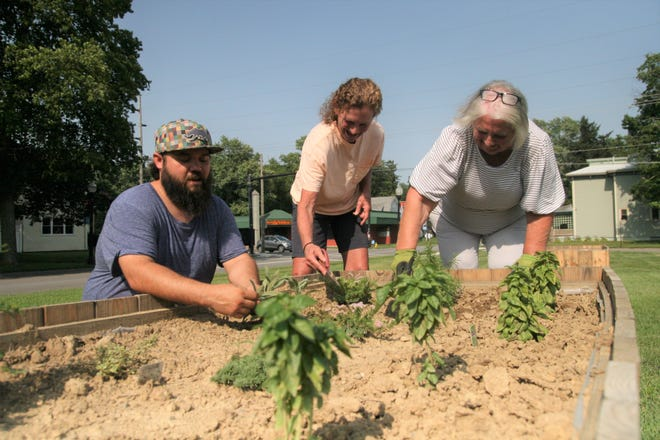 The new community garden in Galion gets manicured, from left, by Zach Morrow, Renee Lillard and Nancy Bittner.