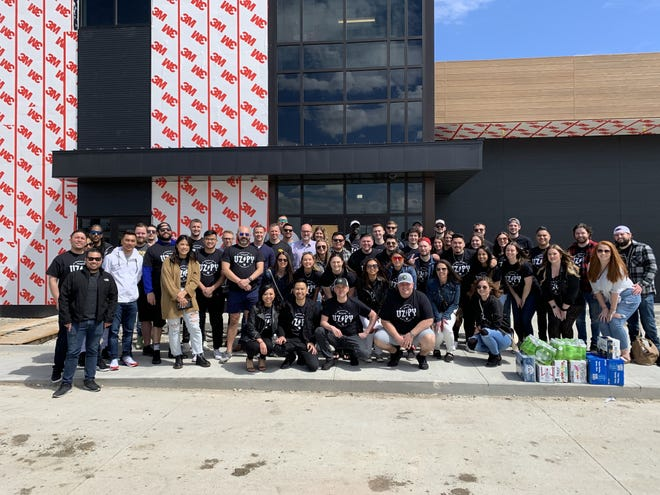 The VizyPay team poses in front of the in-construction building in Waukee.