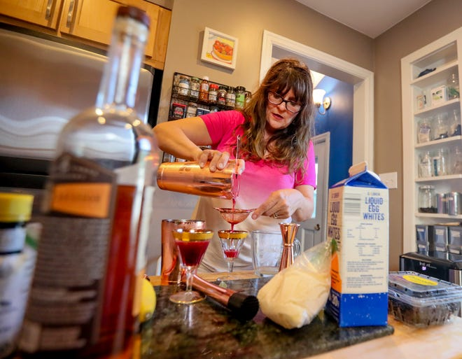 Jeanette Hurt pours her Blackberry Sage Smash. She's doing research for a book on whiskey sours