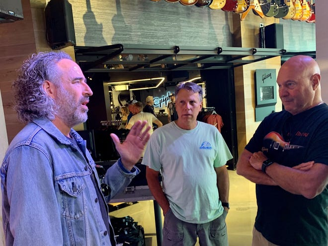 """Gibson Brands President and CEO James """"JC"""" Curleigh speaks with visitors from Florida in the new retail space Gibson Garage in Cummins Station in Nashville July 15, 2021"""