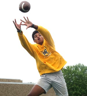 North Farmington High varsity football receiver Aaron Rice leaps for a pass after a July 16, 2021 practice at the school.
