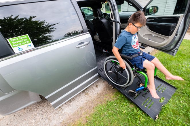 Mason Warner, 9, rolls himself out of his family's new wheelchair-accessible van Thursday, July 15, 2021, at their home in Port Huron. A Port Huron Police officer helped the family fundraise to be able to purchase the van.