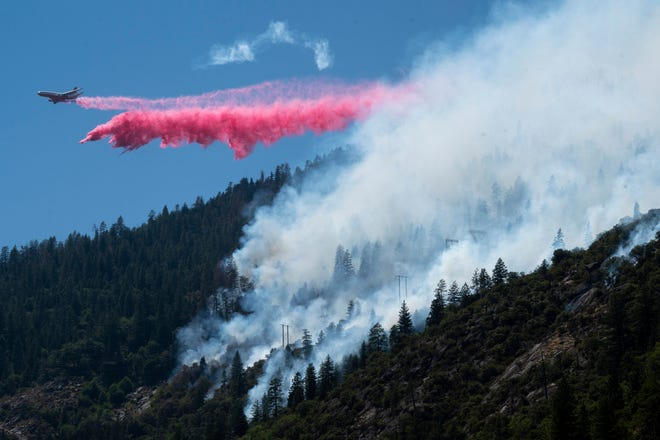 An air tanker drops fire retardant to battle the Dixie Fire in the Feather River Canyon in Plumas County on Wednesday, July 14, 2021. The fire that broke out Tuesday afternoon has chewed through more than 1.8 square miles of brush and timber near the Feather River Canyon area of Butte County.