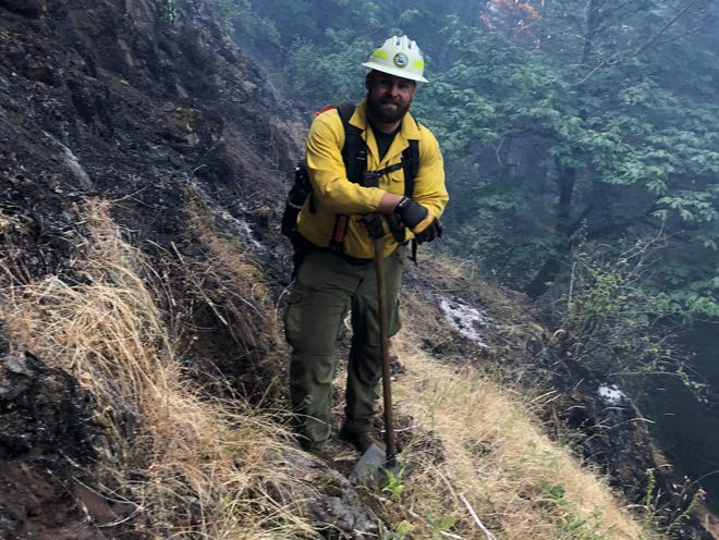 Firefighter Dillon Neumann looks over terrain on the Game Hog Creek Fire for places to put in a containment line. Steep terrain on the fire burning in the Tillamook State Forest has challenged crews.