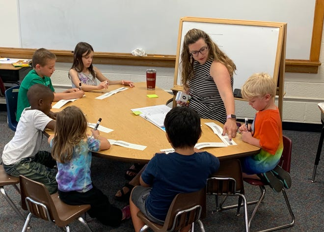 A Sioux Falls teacher works with her students during a summer school class at Garfield Elementary aimed at helping students stay focused on education during the summer break.