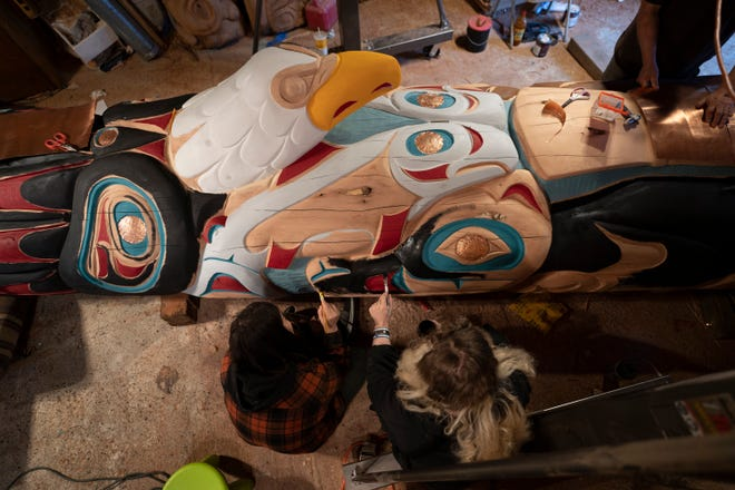 Two artisans of the House of Tears from Lummy work on a 25-foot totem pole that travels the United States with Native American activists to highlight the need to protect holy lands.