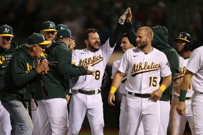 Oakland Athletics' Jed Lowrie (8) is congratulated by teammates after hitting the game-winning home run against Cleveland during the ninth inning of a baseball game in Oakland, Calif., Friday, July 16, 2021. (AP Photo/Jed Jacobsohn)