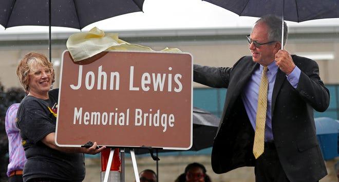 Mayor John Pribonic pulls away a sheet to reveal a sign dedicating the Steels Corners bridge as the John Lewis Memorial Bridge on Saturday in Stow.